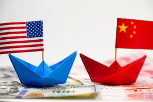 USA flag on blue paper ship and China flag on red paper ship with white background of war trade
